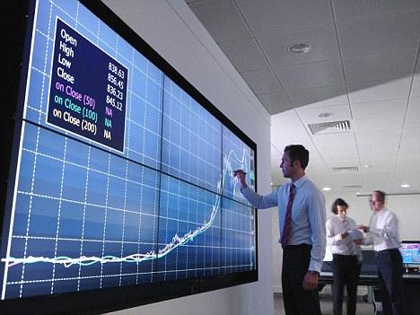 Businessman using graphs on screen --- Image by © Monty Rakusen/cultura/Corbis